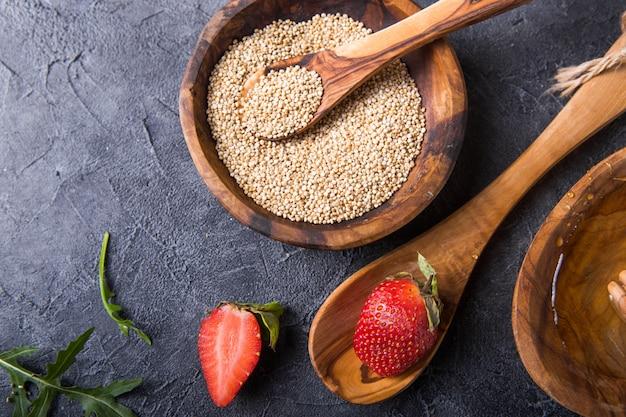 Quinoa grani bianchi in una ciotola di legno e cucchiaio con fragole, miele. senza glutine cibo salutare