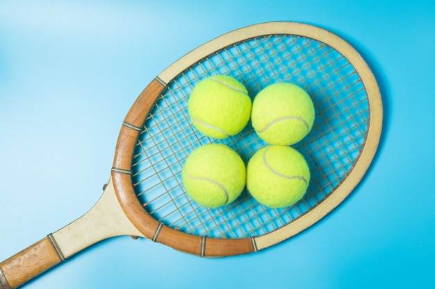 Racchetta da tennis e palle su sfondo blu. equipaggiamento sportivo.