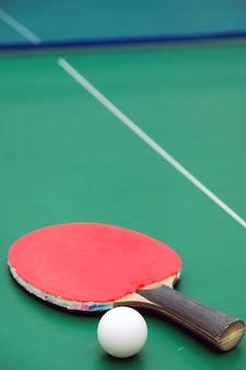 Racchetta di ping-pong con una palla su fondo verde.