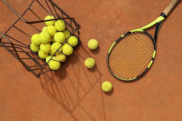 Racchetta e cesto con palline da tennis su campo in terra battuta