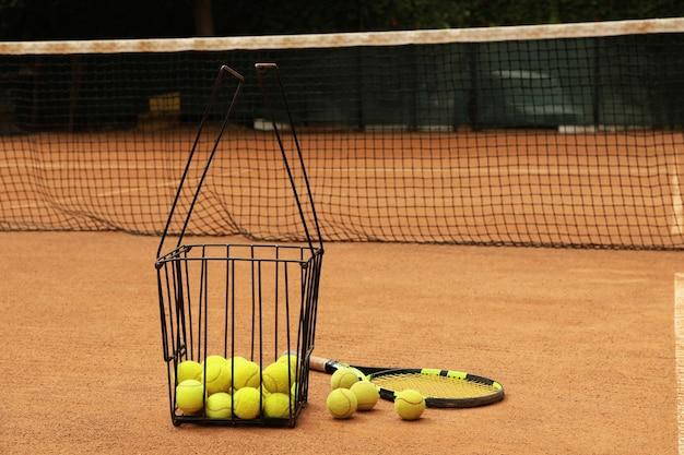 Racchetta e cesto con palline sul campo in terra battuta