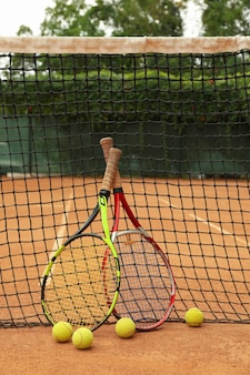 Racchette e palline da tennis contro rete su campo in terra battuta
