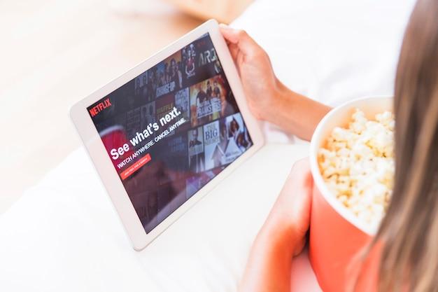 Raccogli la signora con popcorn guardando il sito di netflix