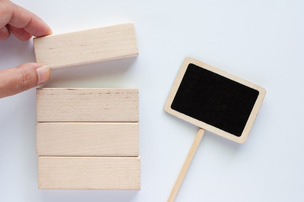Raccogliendo a mano il giocattolo di legno con il bastone dell'etichetta della lavagna