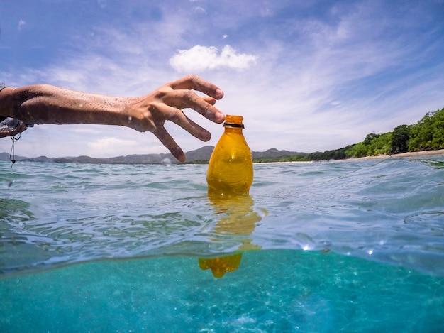 Raccogliendo una bottiglia di plastica dall'ocwan, ricicla