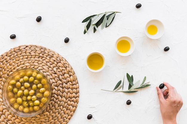 Raccolga a mano l'oliva nera con la fila di olio in ciotola su fondo strutturato bianco