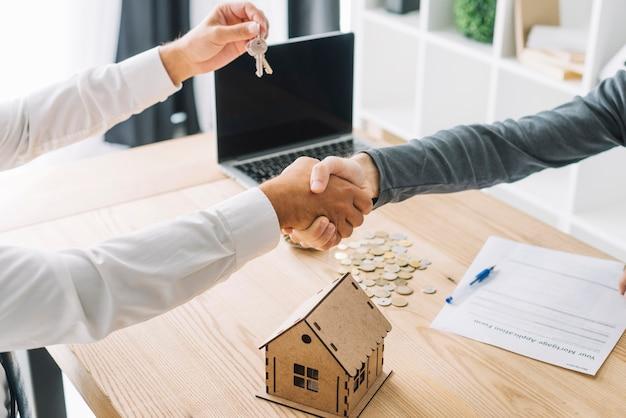 Raccolga gli uomini che si stringono la mano nell'agenzia immobiliare