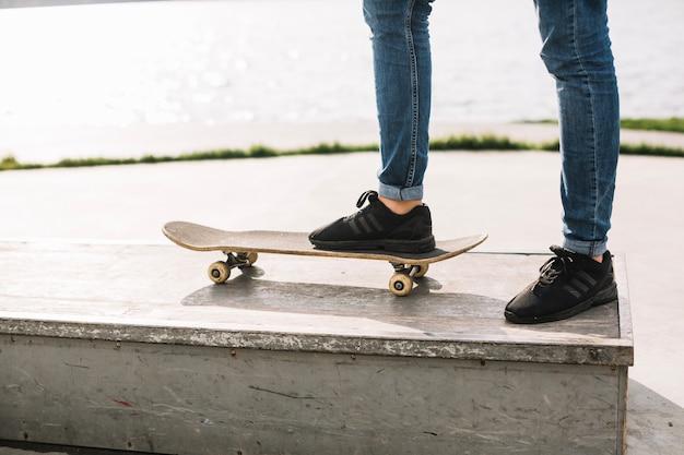 Raccolga l'adolescente che fa un passo sullo skateboard sul bordo