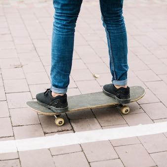 Raccolga l'adolescente sullo skateboard vicino alla pista ciclabile
