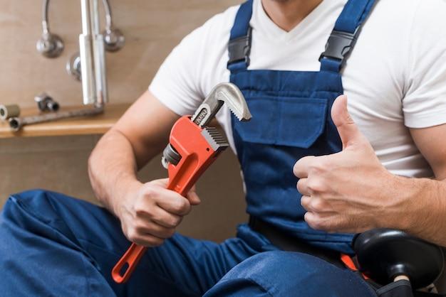 Raccolga l'idraulico che gesturing il pollice su