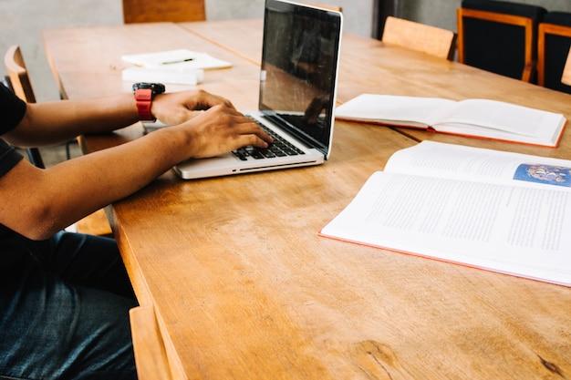Raccolga l'uomo che studia con il computer portatile vicino ai libri