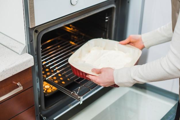 Raccolga la donna che mette la pasticceria nel forno