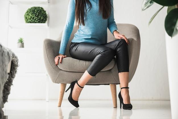 Raccolga la donna che si siede in poltrona