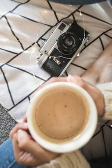 Raccolga la donna con la bevanda calda che si siede vicino alla macchina fotografica