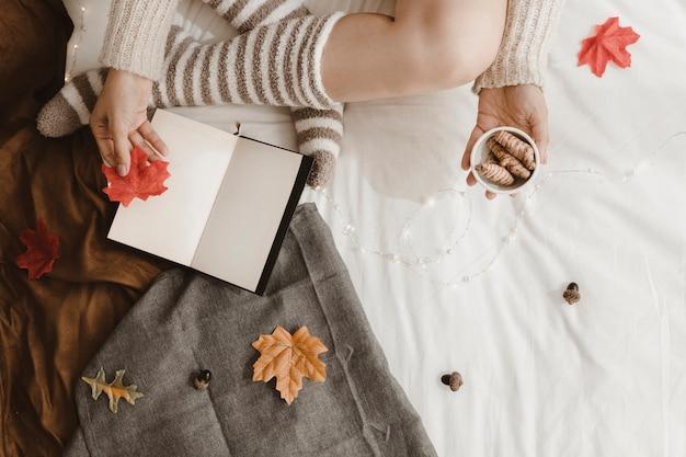 Raccolga la donna con le foglie e lo zenzero vicino al libro