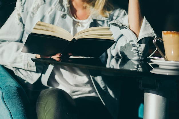 Raccolga la lettura della donna in caffè