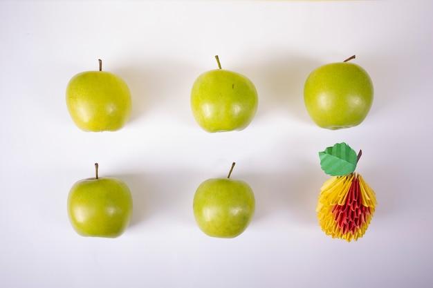 Raccolga le mele di concetto su un'arte di carta elaborata origami della carta fatta a mano del fondo bianco