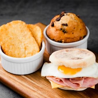 Raccolta del primo piano sandwich dell'uovo di benedict accanto al muffin