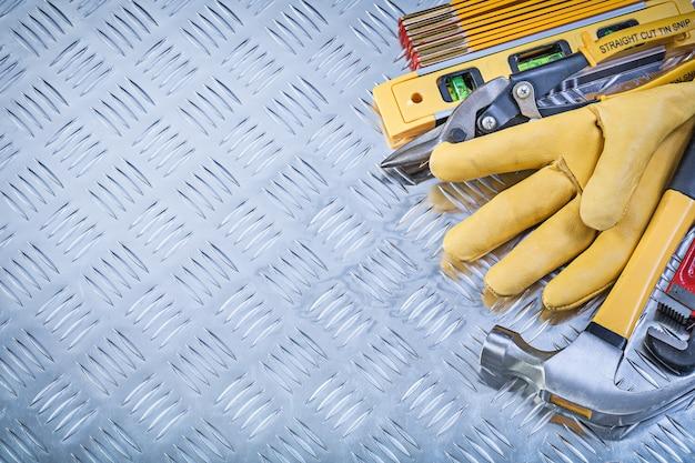 Raccolta della chiave inglese di legno delle chiavi di legno delle pinze del tester della costruzione dei guanti di sicurezza del martello da carpentiere sulla piastra metallica ondulata