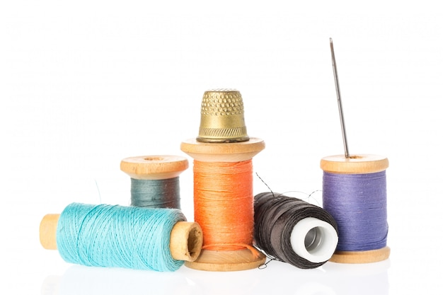 Raccolta delle bobine del filo di colore con l'ago e il ditale isolati su bianco.
