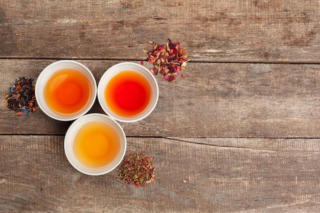 Raccolta di diversi tè in tazze con foglie di tè