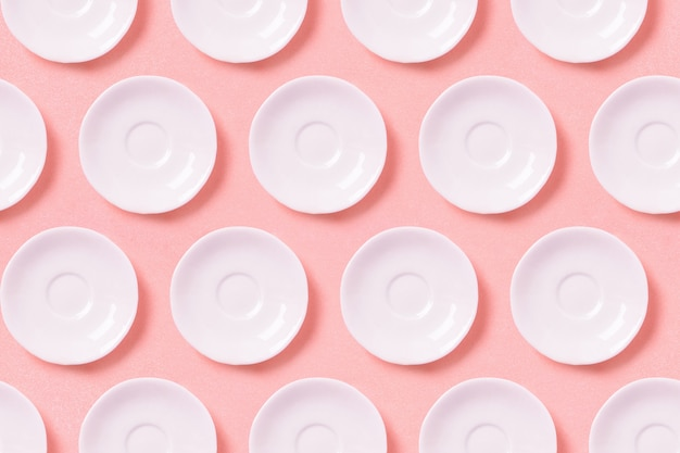 Raccolta di piccoli piatti bianchi su una superficie rosa.