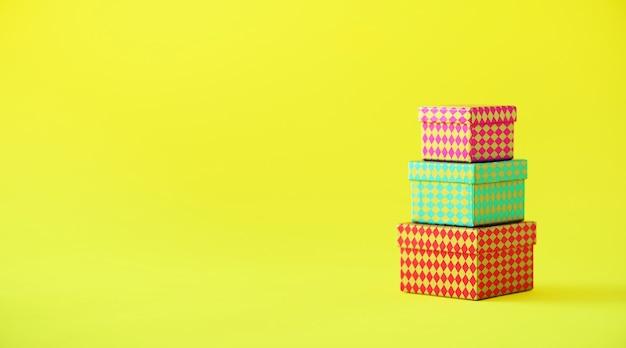Raccolta di scatole regalo colorate su sfondo giallo. banner. regali per la festa di compleanno. natale e anno nuovo concetto