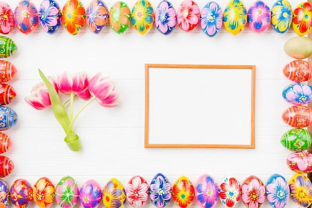 Raccolta di uova colorate su bordi, cornice e fiori