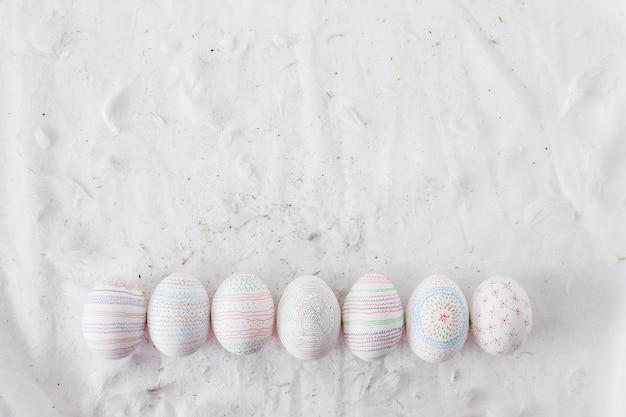 Raccolta di uova di gallina con modelli vicino a spolette sul tessile