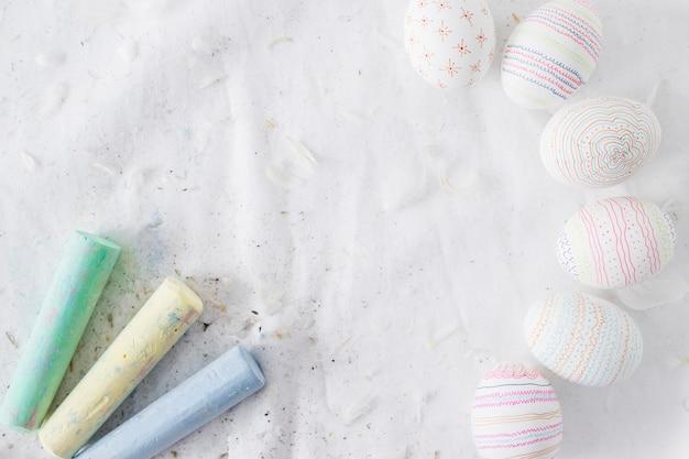 Raccolta di uova di pasqua con disegni vicino a aculei e gessetti sul tessile