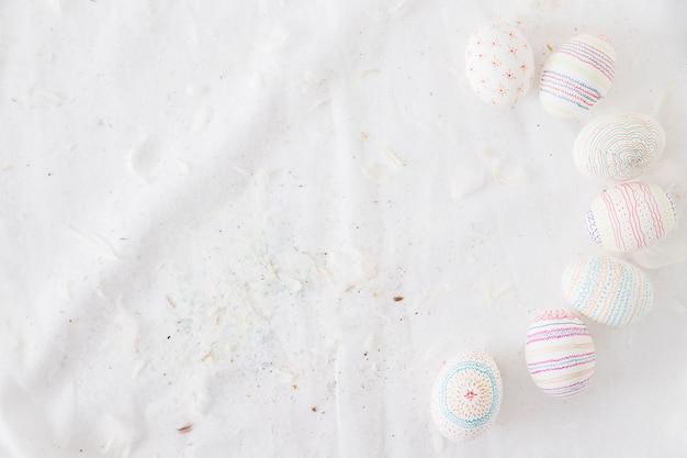 Raccolta di uova di pasqua con modelli vicino piume sul tessile