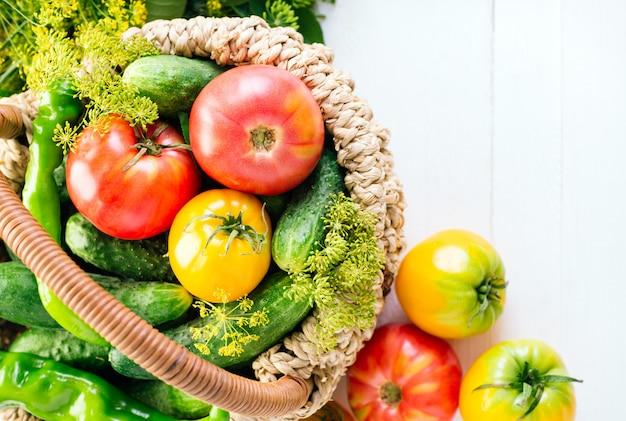 Raccolta di verdure, pomodori, cetrioli e peperoni in un cestino su un legno bianco