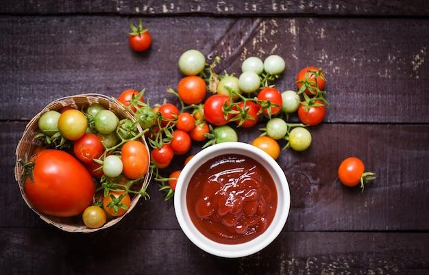 Raccolta organica dei pomodori freschi sul canestro e ketchup in salsa al pomodoro della tazza su buio di legno