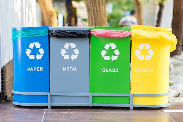 Raccolta selettiva di contenitori colorati con immondizia con iscrizioni per rifiuti separati