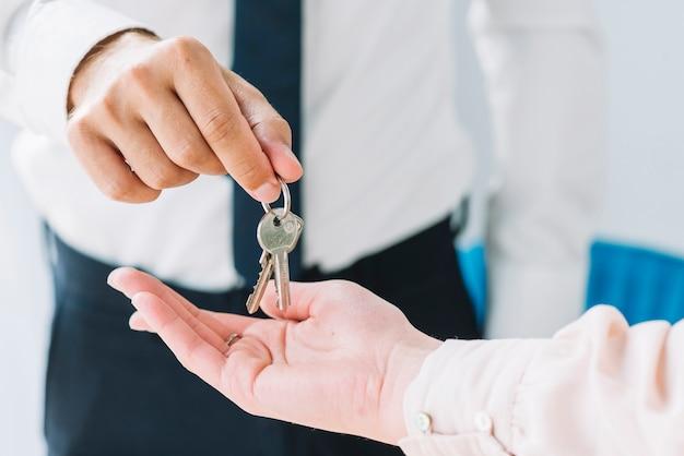 Raccolto agente immobiliare che fornisce le chiavi alla donna