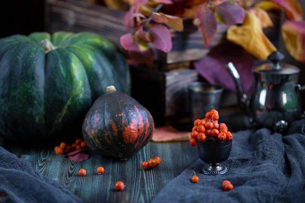 Raccolto autunnale di zucche su un tavolo di legno scuro con foglie di autunno