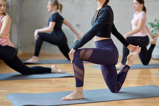 Raccolto di donne che praticano yoga nella hall.
