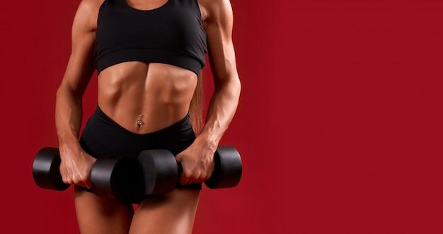 Raccolto di fitnesswoman pompato in posa con manubri.