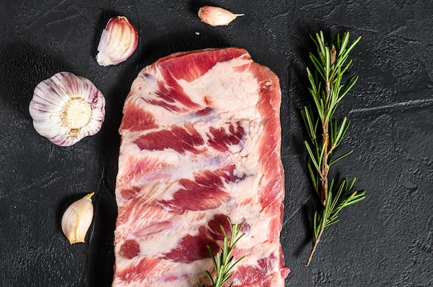 Rack di costine di maiale crudo condito con spezie. sfondo nero. vista dall'alto