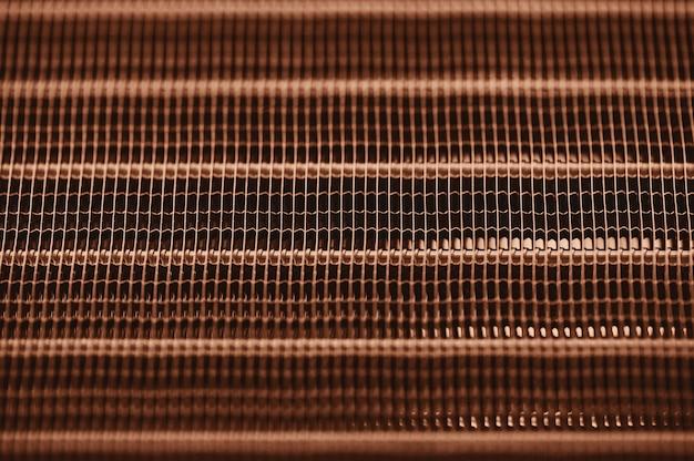 Radiatore dettagliato di raffreddamento ad acqua del motore di struttura con le linee orizzontali. parte arancione dell'automobile con la fine del copyspace in su.