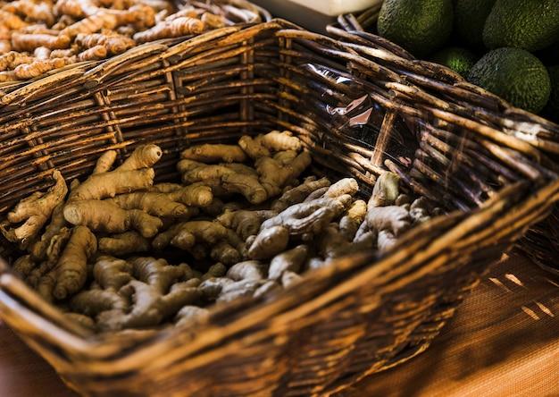 Radici fresche dello zenzero in canestro di vimini marrone al mercato della drogheria