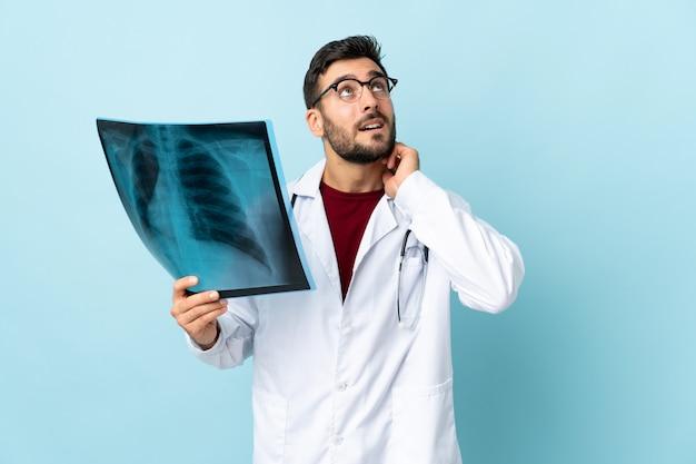 Radiografia professionale della tenuta del traumatologo isolata sulla parete blu che pensa un'idea