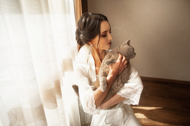 Raduno mattutino della sposa nella bellissima sala luminosa con il suo gatto