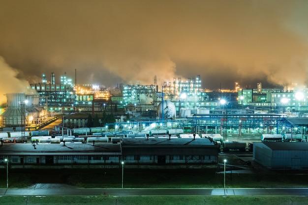 Raffineria di petrolio con tubi e complessi di distillazione durante la notte