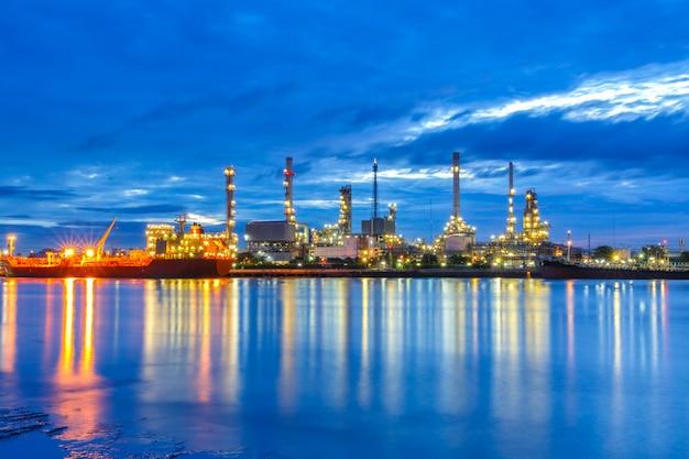 Raffineria di petrolio lungo il fiume al crepuscolo (bangkok, thailandia)