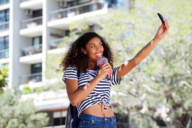 Raffreddi la giovane donna afroamericana che prende il selfie all'aperto