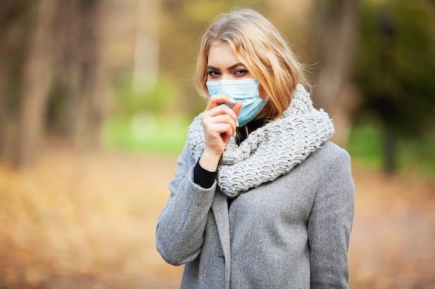 Raffreddore e influenza. donna con una mascherina medica all'aperto