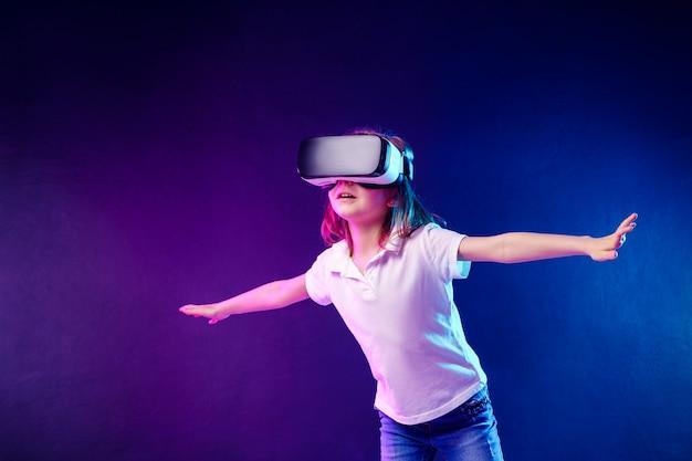 Ragazza 7 anni vivendo il gioco di cuffie vr su colorato. bambino che utilizza un gadget di gioco per la realtà virtuale.