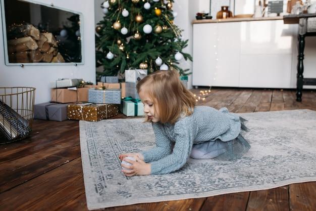 Ragazza a casa che gioca con l'ornamento di natale