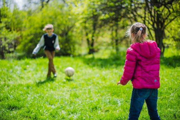 Ragazza a giocare a calcio con suo fratello